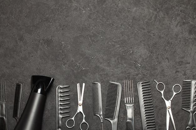 Pettini neri e pettini con le forbici su sfondo nero. copia spazio per il testo.