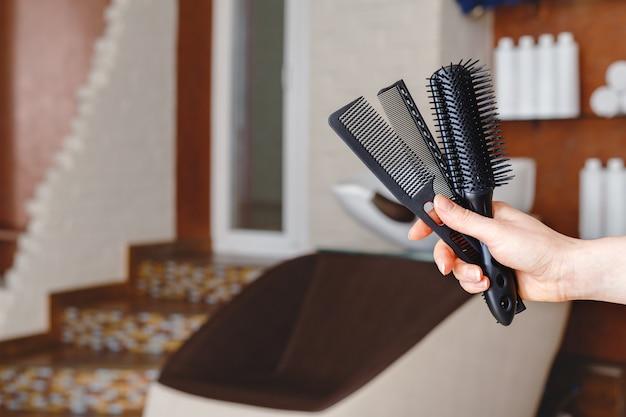 Pettini neri per capelli tagliati in mano femminile contro la sedia del lavandino del lavaggio dei capelli nello studio del salone di bellezza, interno del negozio di barbiere.