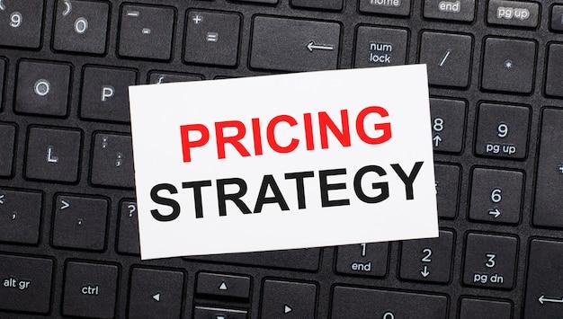 Sulla tastiera di un computer nero c'è una carta bianca con il testo strategia dei prezzi. vista dall'alto