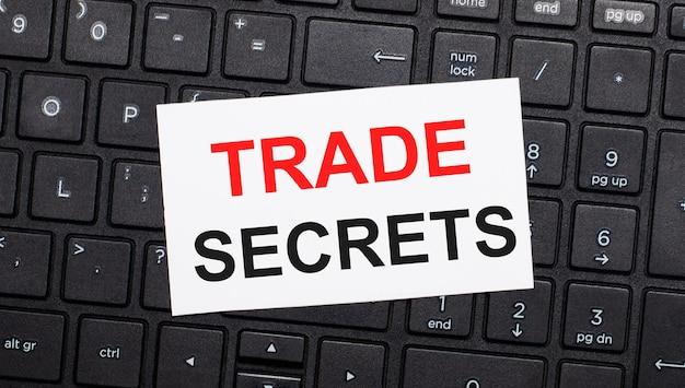 Sulla tastiera di un computer nero c'è una carta bianca con il testo segreti commerciali. vista dall'alto