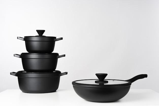 Pentole da cucina nere su sfondo grigio vista frontale da vicino