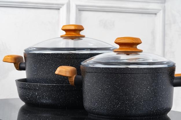 Pentole nere sul fornello a induzione contro il muro grigio