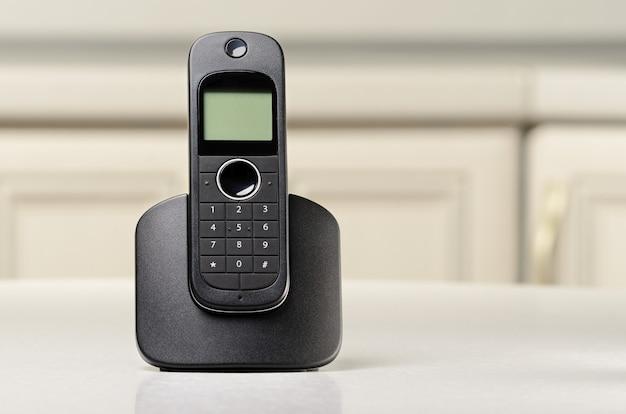 Telefono cordless nero in piedi su un tavolo