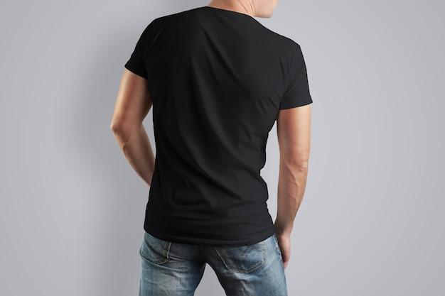 Maglietta di cotone nera su un uomo in posa su un muro grigio