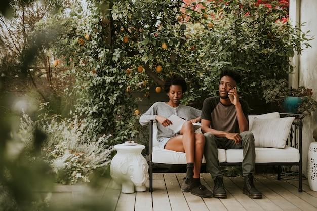 Coppia nera appesa in giardino con un libro e uno smartphone