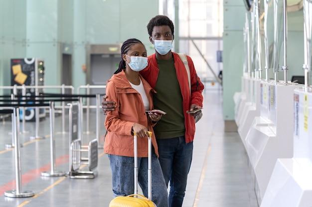 Coppia nera in maschere mediche con passaporto per i bagagli in aeroporto viaggia al sicuro durante la pandemia di covid