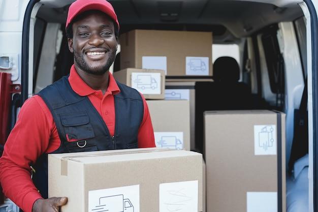 Uomo di corriere nero consegna pacco davanti al camion del carico - focus sul viso