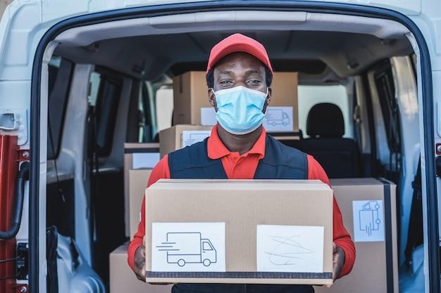 Uomo di corriere nero consegna pacco davanti al camion del carico che indossa la maschera di sicurezza - focus sul viso