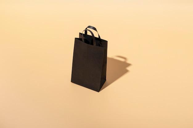 Borsa artigianale nera con manici neri su fondo beige. venerdì nero concetto. grande vendita