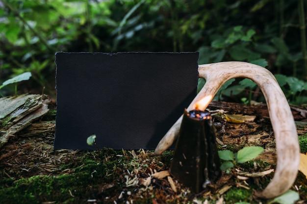 Candela nera mockup di carta artigianale nera sullo sfondo della natura magica della foresta