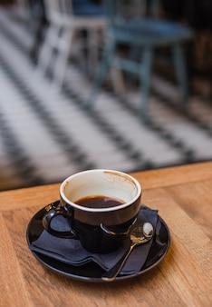 Una tazza nera di caffè espresso mezzo pieno sul tavolo di legno al mattino