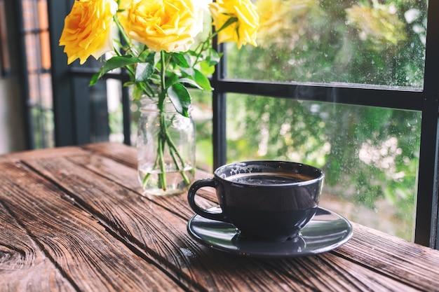 Una tazza nera di caffè caldo e rose gialle in un vaso sul tavolo di legno d'epoca