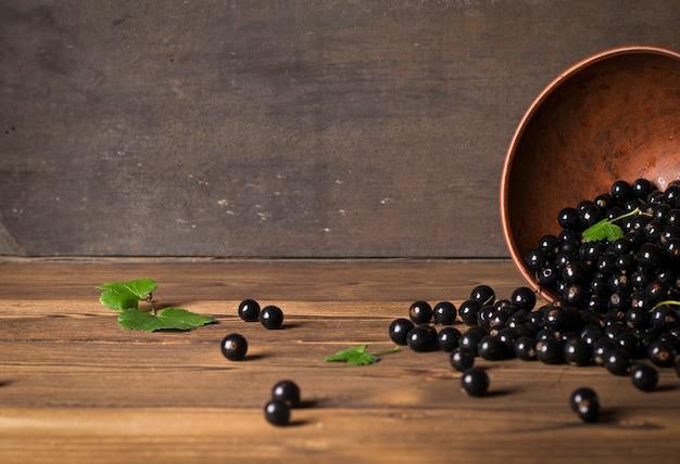 Ribes nero sul tavolo di legno con rametto di foglie