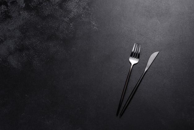 Posate nere su un tavolo scuro di cemento. preparazione del tavolo da pranzo