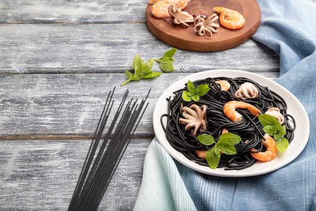 Pasta al nero di seppia con gamberi o gamberi e polpi su fondo di legno grigio e tessuto blu. vista laterale,