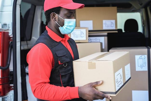 Uomo di consegna nero che indossa una maschera di sicurezza per la prevenzione del coronavirus - focus sul viso