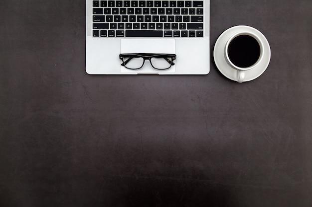 Scrivania nera con notebook bianco e altri articoli per ufficio.