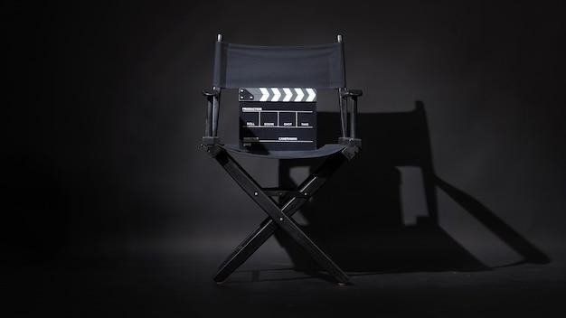 Sedia regista nera e clapper board o film clapperboard su sfondo nero.utilizzare nella produzione video o nell'industria cinematografica