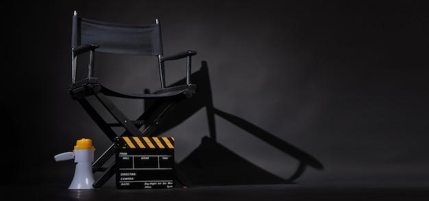 Sedia regista nera e ciak o ciak film con megafono su sfondo nero. utilizzare nella produzione video o nell'industria cinematografica