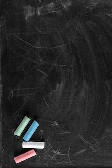 Struttura nera della lavagna sporca con diversi pezzi di gesso di colori, copia dello spazio