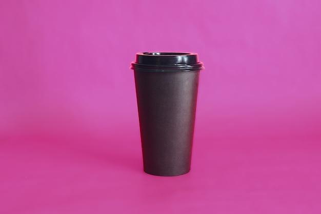 Tazza di caffè usa e getta nera sul rosa.