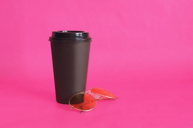 Tazza da caffè usa e getta nera e occhiali da sole alla moda con montature dorate su rosa.