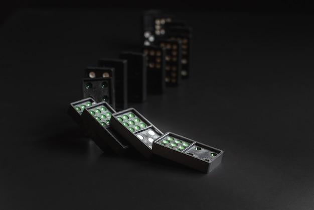 Domino neri che cadono sullo sfondo nero. il gioco del domino. affari modello