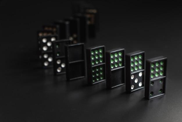 I domino neri si posizionano sullo sfondo nero. il gioco del domino. affari modello