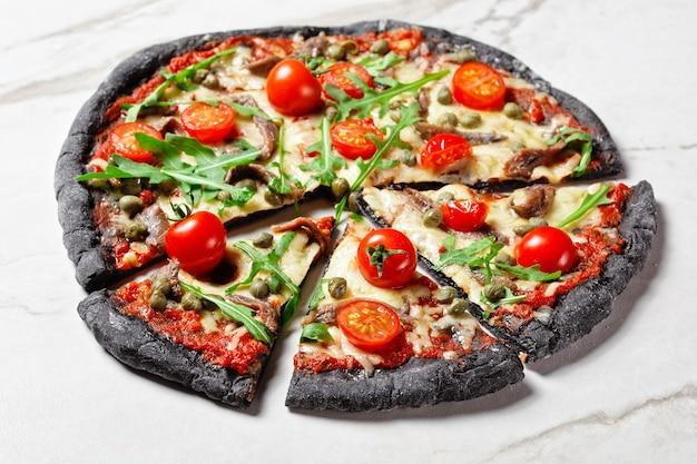 Pizza di pasta nera con acciughe, mozzarella fusa, pomodoro, rucola e capperi su un tavolo di marmo, vista orizzontale dall'alto