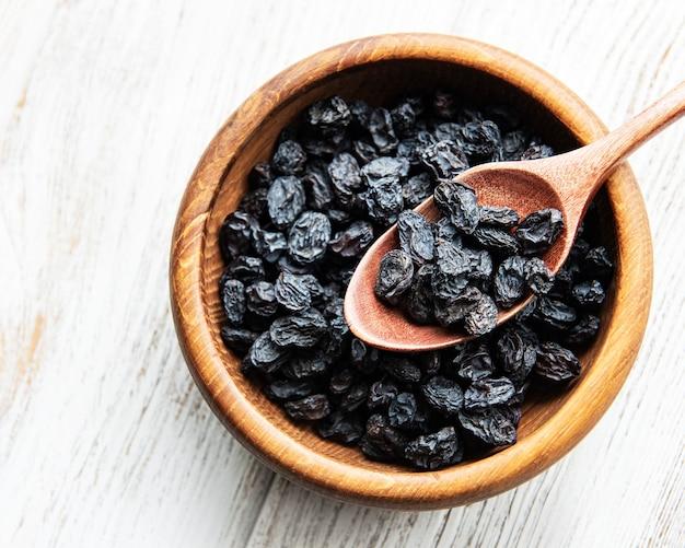Uva passa secca nera su una superficie di legno bianca
