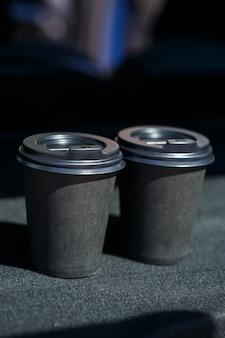 Bicchieri in carta ecologica nera per portare con te il caffè. due tazze di tè caldo con coperchio