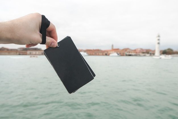 Scheda vuota nera nella mano di un uomo sul paesaggio del mare. concentrati su una carta nera