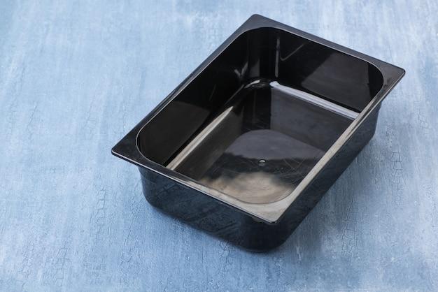 Contenitore di plastica vuoto nero per gelato, vista dall'alto
