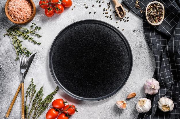 Piatto vuoto nero nel centro di verdure crude fresche
