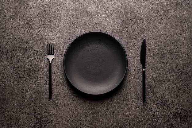 Piatto vuoto nero e posate forchetta e coltello su un concetto di mockup di sfondo scuro testurizzato per la progettazione di un sito web o design di un menu di ristorante