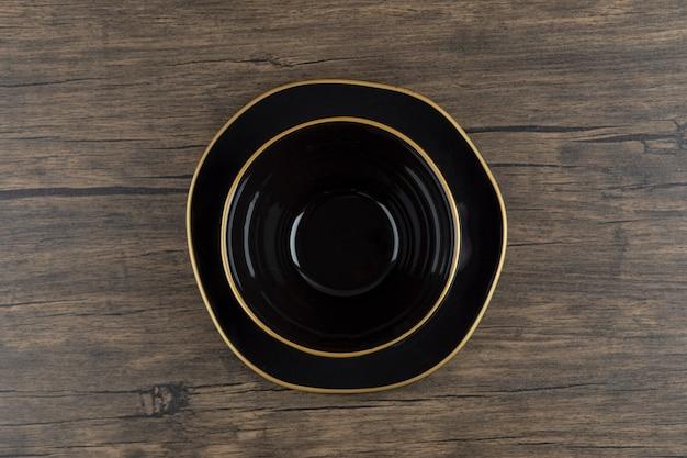 Ciotola e piatto di minestra vuoti neri su superficie di legno.