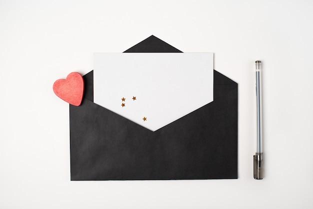 Busta nera con un foglio di carta bianco all'interno, cuore di legno rosso e una penna sullo sfondo chiaro (bianco)
