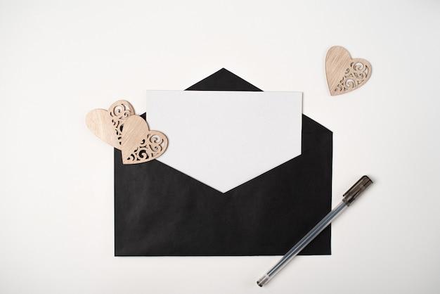 Busta nera con all'interno un foglio di carta bianco, cuori di legno e una penna sullo sfondo chiaro (bianco)