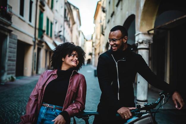 Coppia etnica nera con biciclette per le strade di una città italiana.