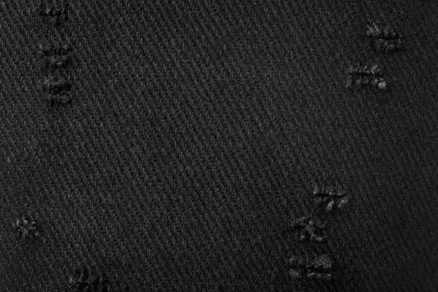 Trama del tessuto nero. sfondo di materiale scuro realizzato con un panno. tessuti strappati.