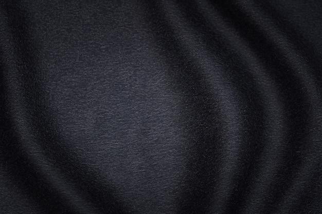 Fondo di struttura del tessuto nero, colore nero sdrucciolevole del tessuto ondulato, raso di lusso o struttura del panno di seta o lana.