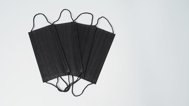 Maschera facciale nera o gruppo di maschera monouso nera per l'orecchio su sfondo bianco.