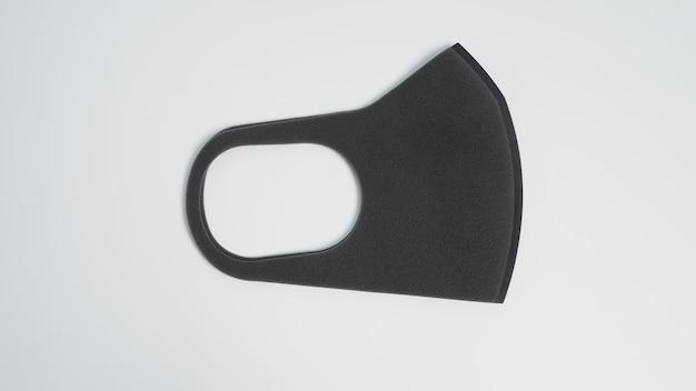 La maschera facciale nera aiuta a proteggere il virus covid-19, la polvere e altre particelle su sfondo bianco.