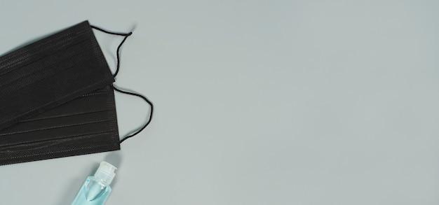 Maschere per il viso nere e gel alcolico su sfondo grigio. protezione contro covid-19, influenza e altre infezioni trasmesse per via aerea. copia spazio