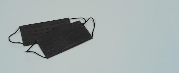 Maschere per il viso nere su sfondo grigio. protezione contro covid-19, influenza e altre infezioni trasmesse per via aerea. copia spazio