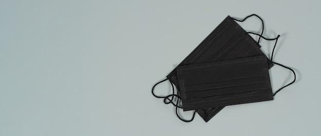 Maschere per il viso nere su sfondo grigio. protezione contro covid-19, influenza e altre infezioni trasmesse per via aerea. copia spazio Foto Premium