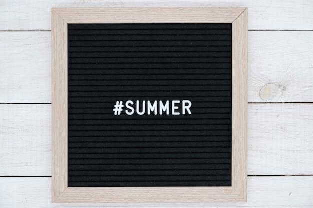 Lavagna in feltro nero con hashtag e parola estate in inglese sul tavolo di legno bianco