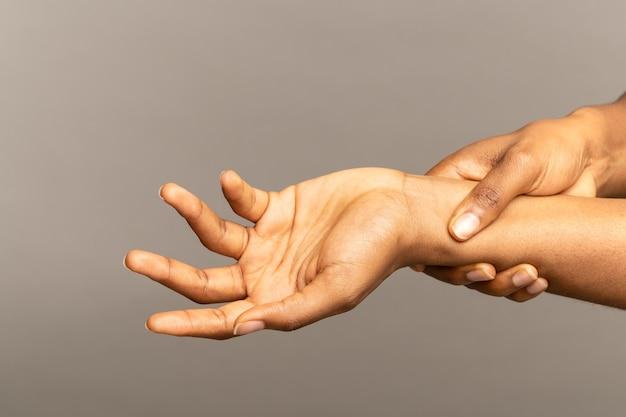 Braccia femminili nere che massaggiano il polso doloroso che soffre di debolezza e formicolio malattia da lesioni sportive