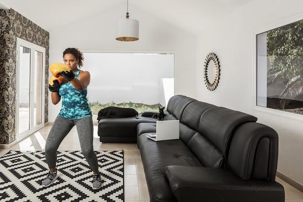 Atleta nera in abbigliamento sportivo e guantoni da boxe che fa esercizi durante l'allenamento a casa con i cani