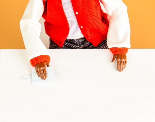La bambola femmina nera tiene una piccola maschera facciale e si siede al tavolo